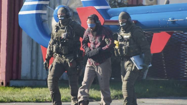 Mounir el Motassadeq (Mitte) wird mit verbundenen Augen aus einem Helikopter gebracht.