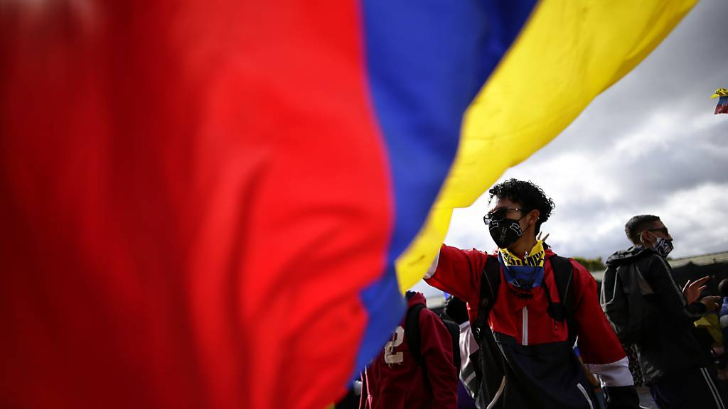 Junge Demonstranten schwenken eine riesige Fahne von Kolumbien während eines neuen Protests gegen die Regierung von Präsident Duque inmitten der Corona-Pandemie. Foto: Fernando Vergara/AP/dpa