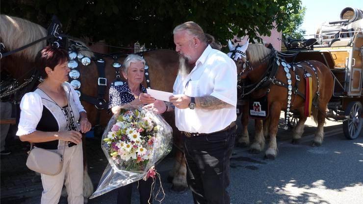 Gemeindepräsident Brandon Miller gratuliert Susanne Michel zusammen mit Gemeindeschreiberin Annemarie Wüthrich.