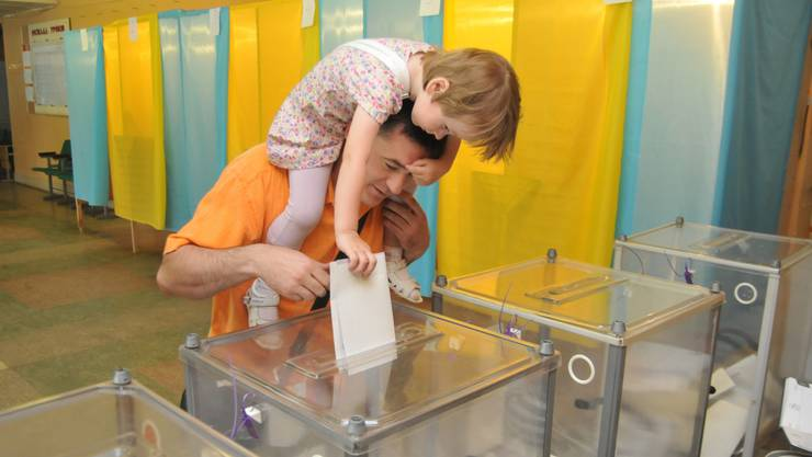 Ein Wähler lässt seine Tochter das Stimmcouvert in die Urne werfen.