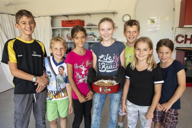 Die Kinder freuen sich über den Kuchen, den sie selbst gebacken und dekoriert haben.