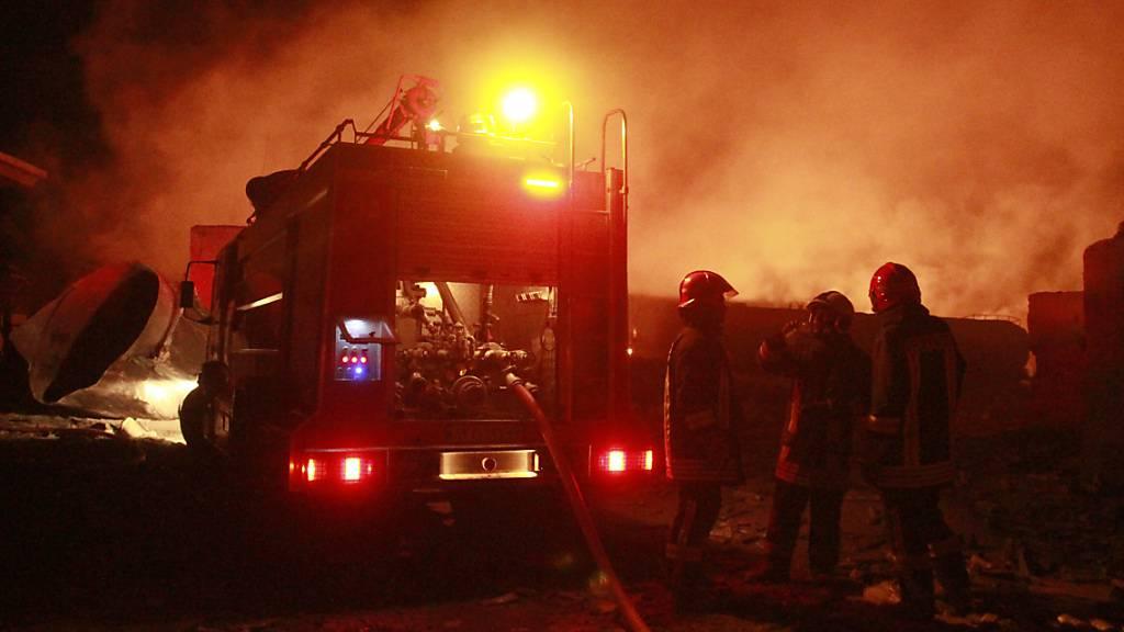 Iranische Feuerwehrleute arbeiten an einem brennenden Tankwagen mit Kraftstoff an der Islam Qala Grenze zum Iran, in der Provinz Herat, westlich von Kabul. In einer Grenzstadt im Westen Afghanistans sind Hunderte Gastankwagen einem Flammeninferno zum Opfer gefallen. Am Samstagmittag explodierte nahe der Grenze zum Iran aus noch ungeklärter Ursache ein Tankwagen und löste eine Kettenreaktion au Foto: Hamed Sarfarazi/AP/dpa