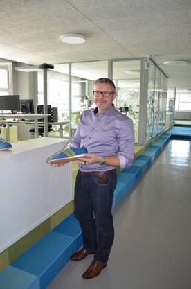 Karsten Bugmann präsentiert die Künzli-Schuhe in Spitex-Farben, die jeder Mitarbeitende zum 5-Jahrjubiläum erhält.