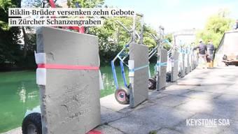 """Mit Hammer und Meissel schlugen die Konzeptkünstler Frank und Patrik Riklin in der St. Galler Altstadt ihre """"Zehn Gebote, Teil 2"""" in Sandsteintafeln. Zum Abschluss ihrer Aktion versenkten sie die Tafeln im Zürcher Schanzengraben, gleich neben dem Herz der Schweizer Finanz- und Bankenwelt."""