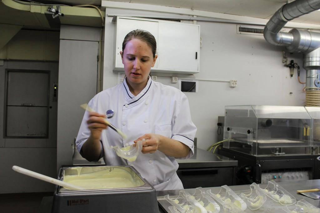Die Verzierung, hier durch Abteilungsleiterin Melanie Näf, mit schwarzer und weisser Schokoladenüberzugsmasse ist der erste Schritt bei der Herstellung eines Osterhasen. (© FM1Today/Felix Unholz)