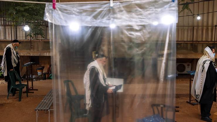 dpatopbilder - Ultraorthodoxe Juden halten den nötigen Mindestabstand ein und tragen Mundschutz, während eines Morgengebets vor ihren Häusern, da in den Synagogen nur maximal zwanzig Personen gleichzeitig beim Gebet zugelassen sind. Foto: Oded Balilty/AP/dpa