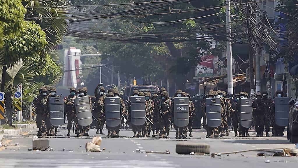 Einsatzkräfte des Militärs mit Schutzschilden bewegen sich während eines Protests in Rangun eine Straße hinauf. Foto: Uncredited/AP/dpa