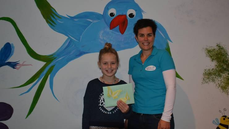 Die glückliche Ballonflug-Wettbewerb-Gewinnerin Noëlle Meier aus Erlinsbach erhält von Rebecca Lässer, Präsidentin Spielgruppe Paradiesli, einen Gutschein.