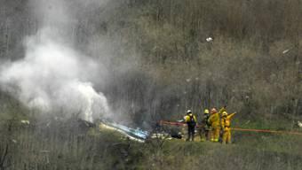 Feuerwehrleute löschen den abgestürzten Helikopter.