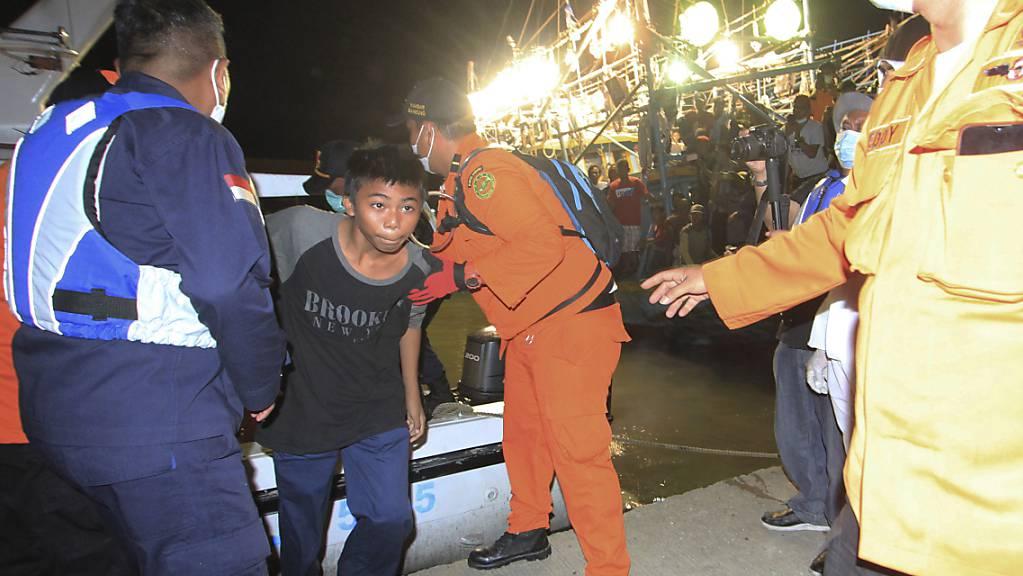 Rettungskräfte helfen einem der Überlebenden des Schiffsunglücks bei seiner Ankunft im Hafen von Indramayu. Foto: Panji Wisnu/AP/dpa