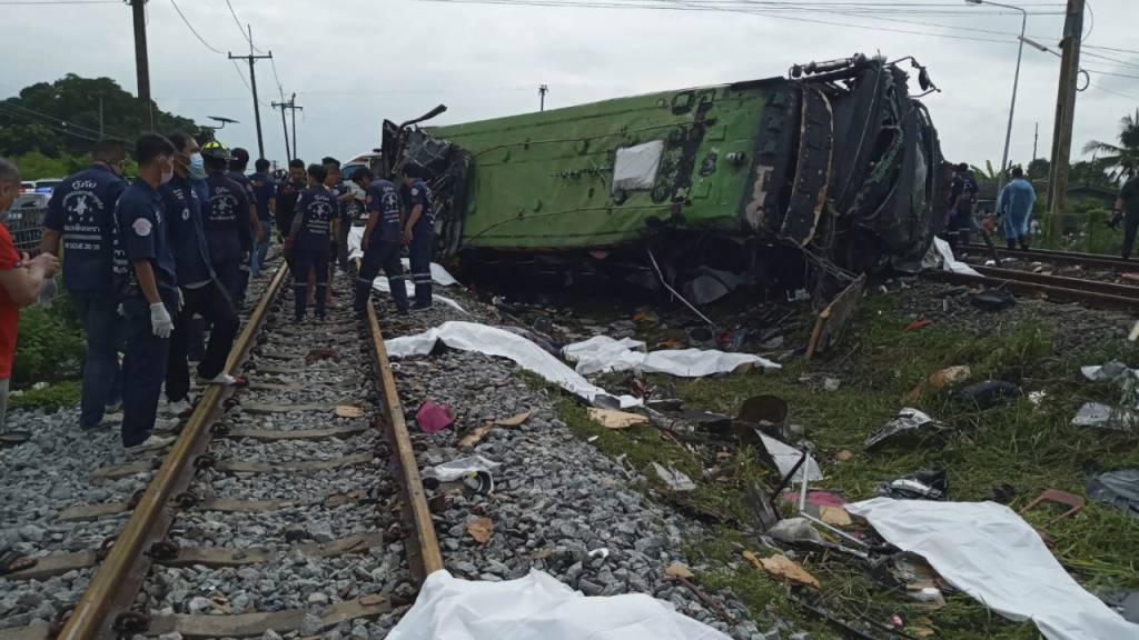 Rettungskräfte stehen an einem beschädigten Zug und neben mit weißen Tüchern bedeckten Leichen. Mindestens 17 Menschen sind am Sonntag in Thailand beim Zusammenstoß eines Busses mit einem Zug ums Leben gekommen. Weitere 30 Menschen wurden bei dem Unfall verletzt. Foto: Uncredited/Daily News/AP/dpa