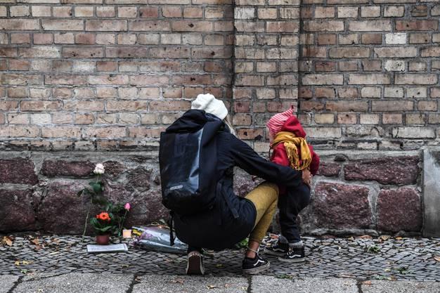 Eine Frau und ihr Kind vor den Kerzen und Blumen für die Verstorbenen in Halle.