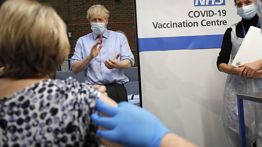 ARCHIV - Boris Johnson (M), Premierminister von Großbritannien, applaudiert, nachdem die Krankenschwester Rebecca Cathersides (r) zu Beginn der britischen Impfkampagne den Pfizer-BioNTech Corona-Impfstoff an Lyn Wheeler (l) im Guy's Hospital verabreicht hat. Foto: Frank Augstein/AP POOL/dpa