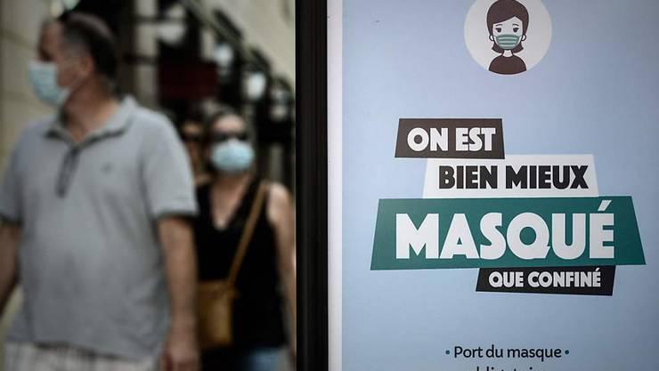 Passanten sind hinter einem Plakat mit der Aufschrift «On est bien mieux masqué que confiné» (Lieber maskiert als eingesperrt) zu sehen. Foto: Philippe Lopez/AFP/dpa