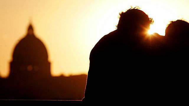 Ein Liebespaar geniesst einen Sonnenuntergang in Rom - im Hintergrund der Petersdom (Archiv)