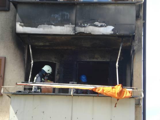Brandermittler auf dem Balkon der ausgebrannten Wohnung