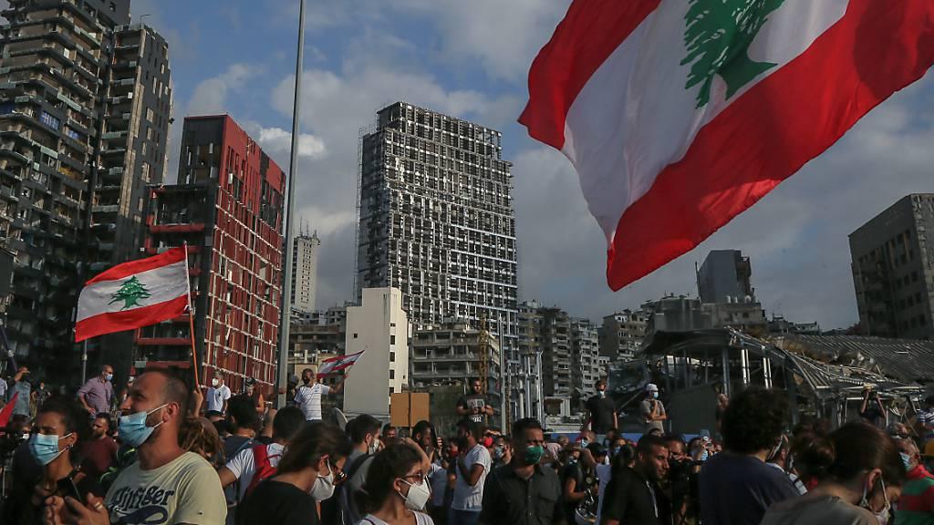 Regierungskritische Demonstranten nehmen an Demonstranten mit der Fahne des Libanon Mitte August bei einem Trauermarsch für die Opfer der verheerenden Explosion von Beirut.