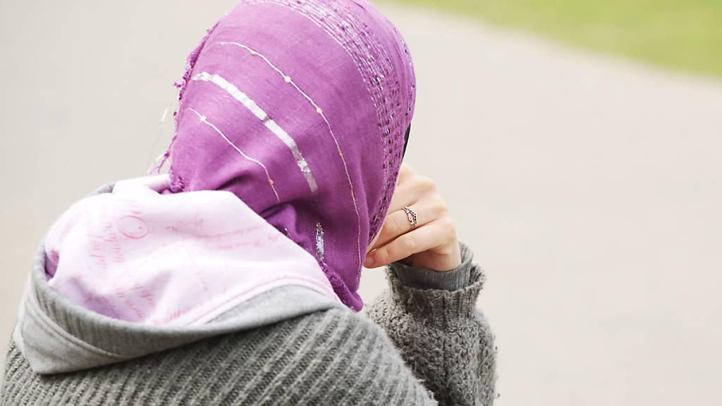 ARCHIV - Eine junge Frau mit Kopftuch sitzt an einem Weg. Am Donnerstag hatte der Europäische Gerichtshof (EuGH) vor dem Hintergrund von zwei Streitfällen in Deutschland entschieden, dass ein Kopftuchverbot gerechtfertigt sein kann. Diese Entscheidung verurteilt die Türkei. Foto: Wolfram Steinberg/dpa