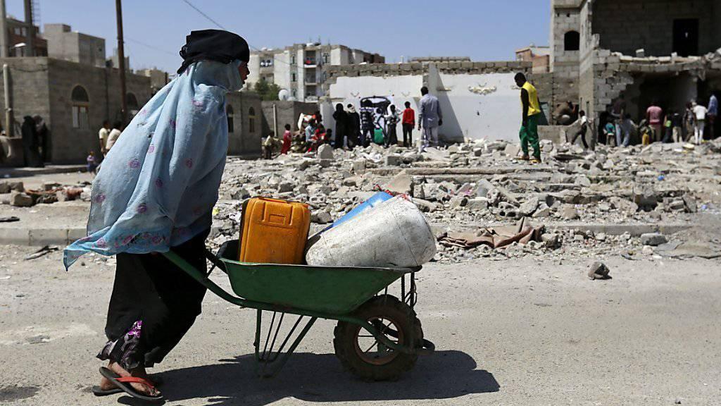 Eine jemenitische Frau holt Wasser in ihrer vom Bürgerkrieg zerstörten Stadt. Im Jemen kämpfen schiitische Houthi-Rebellen gegen Regierungstruppen, die von einer sunnitischen Koalition unter Führung Saudi-Arabiens unterstützt werden.