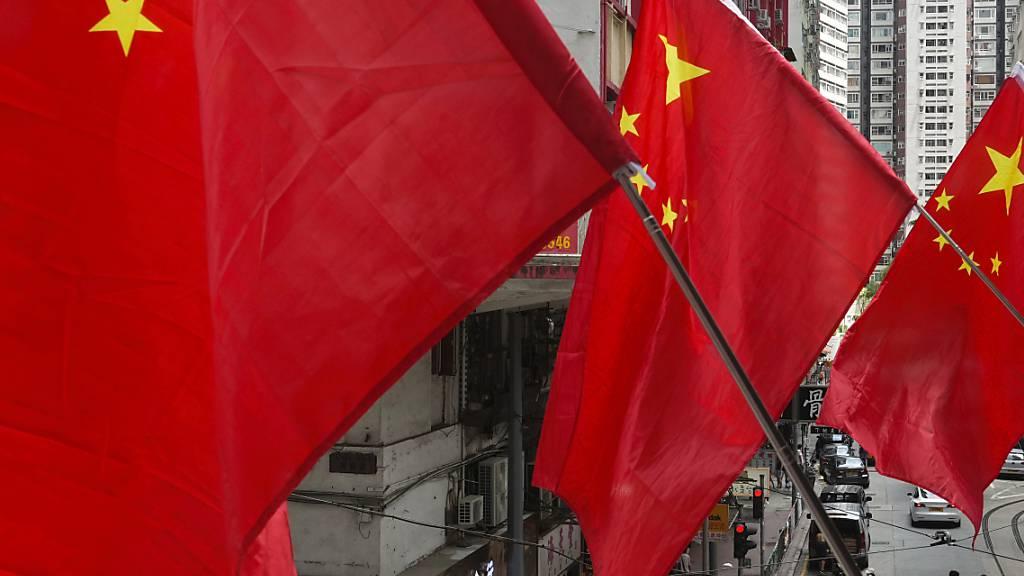 Menschen laufen unter chinesischen Flaggen, die als Teil einer Flaggenzeremonie aufgestellt wurden. Foto: Vincent Yu/AP/dpa/Symbolbild