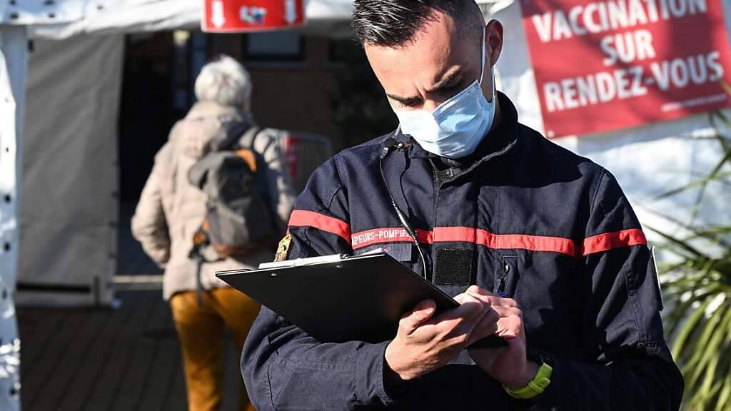 Ein Feuerwehrmann mit Mund-Nasen-Bedeckung steht vor einer Feuerwehrwache im französischen Vailhauquès, die in ein temporäres Corona-Impfzentrum umgewandelt wurde. Foto: Pascal Guyot/AFP/dpa