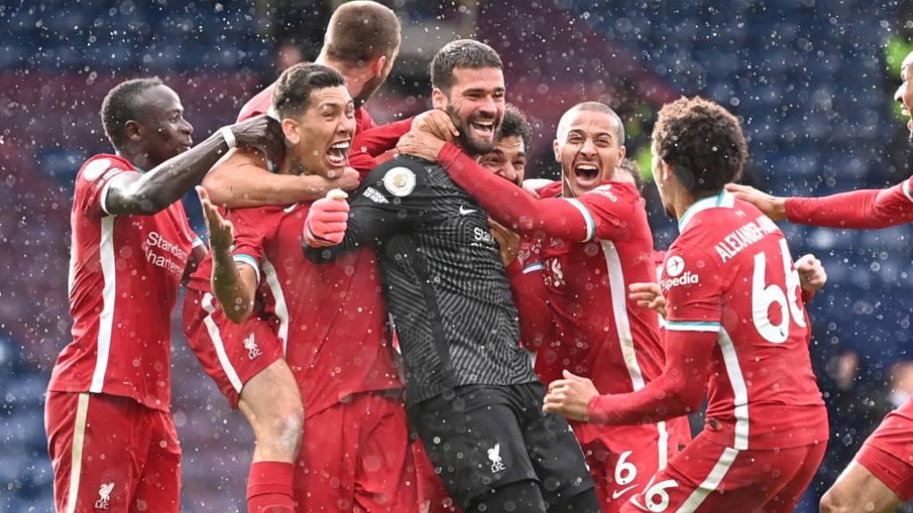 Die Liverpooler feiern Goalie Alisson und dessen späten Siegtreffer