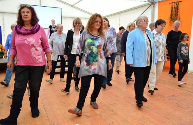 Die 66-jährige Liliane Dürr (ganz links) und etwa zwanzig weitere Besucherinnen und Besucher stellen beim Line-Dance Schnupperkurs ihre Agilität unter Beweis.