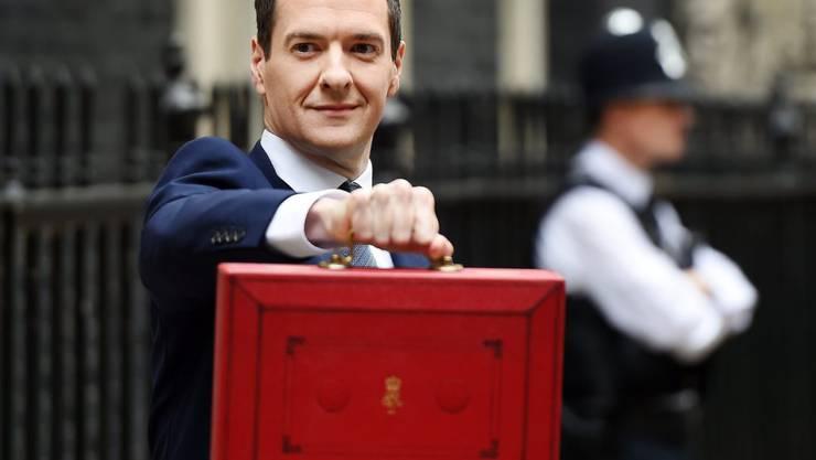 Finanzminister George Osborne auf dem Weg zum Parlament, in der Hand das traditionelle rote Köfferchen, in welchem sich die Unterlagen für den Budgetentwurf befinden.