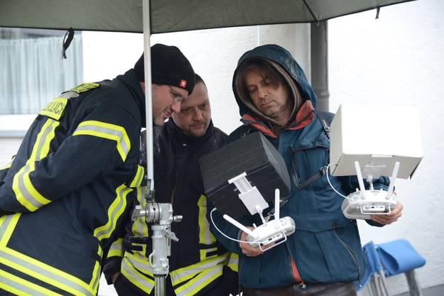 uch Drohnen stehen im Einsatz, Feuerwehrleute begutachten die Aufnahmen.