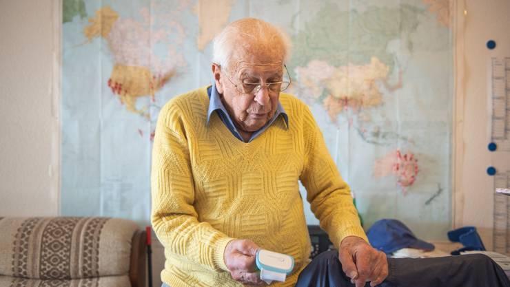 Der 92-jährige Theodor Lips zeigt den Sensor, den er im Rahmen der «Strong-Age»-Studie ein Jahr lang täglich um den Oberarm trug.