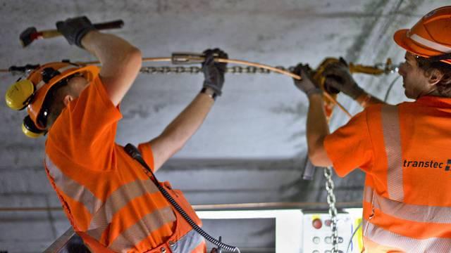 Zwei Arbeiter bauen Teile der Bahntechnik in den Gotthard-Basistunnel ein (Archiv)