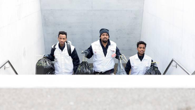 Mogos A., Meresh S. und Luul W. entsorgen nach der Zugsreinigung die Abfälle.