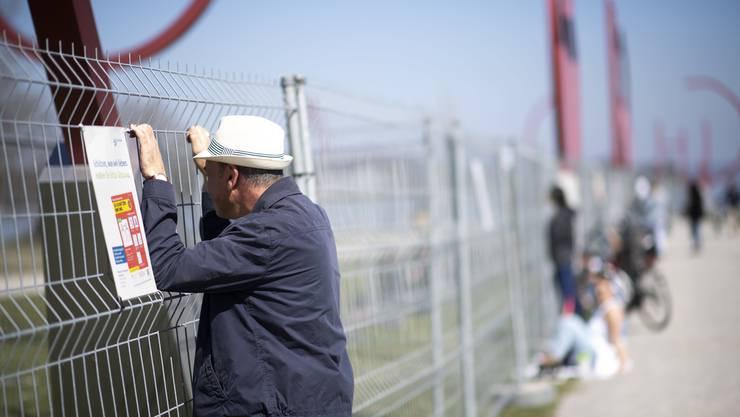 Menschen sprechen miteinander durch einen Zaun an der Grenze zwischen der Schweiz und Deutschland in Kreuzlingen.