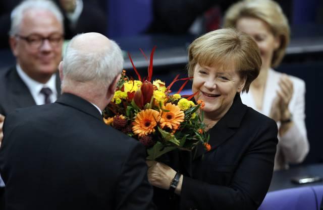Die wiedergewählte Bundeskanzlerin Angela Merkel erhält Blumen