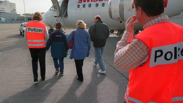 Eine ausreisewillige Familie wird zum Flugzeug begleitet (Symbolbild)