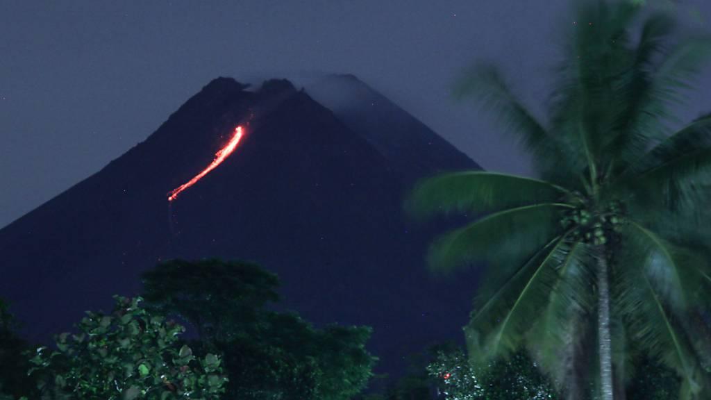 Glühende Lava fliesst aus der Vulkanspitze des Merapi auf Java.
