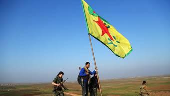 YPG-Milizionäre hissen die Flagge von syrisch-Kurdistan bei Kobane.