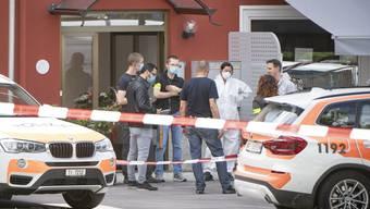 Die Polizei und Forensiker bei einem Restaurant am Rande der Piazza Grande von Giubiasco, wo eine Schiesserei mit drei Toten stattfand.