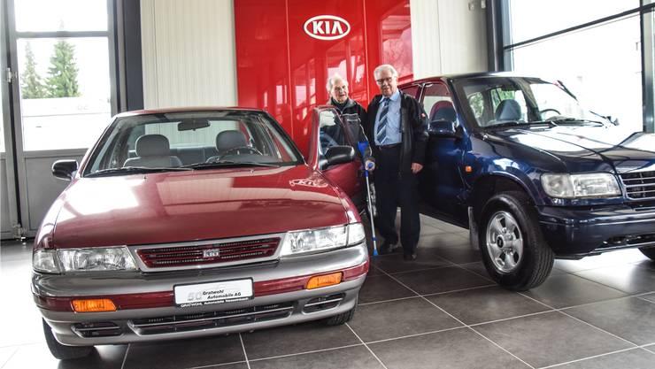 Theodor Seiler und Franz Gratwohl mit dem ersten in der Schweiz verkauften KIA Sephia, rechts ein KIA Sportage, ebenfalls ein Auto aus der ersten Modellreihe.