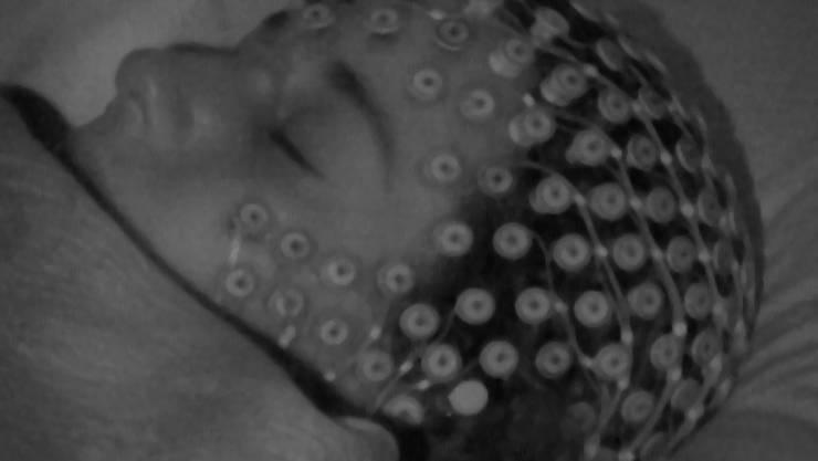 Mithilfe von 256 Elektroden haben Forschende die Hirnaktivität von Probanden im Schlaf überwacht und dabei entdeckt, woran man das Träumen im Gehirn erkennen kann.