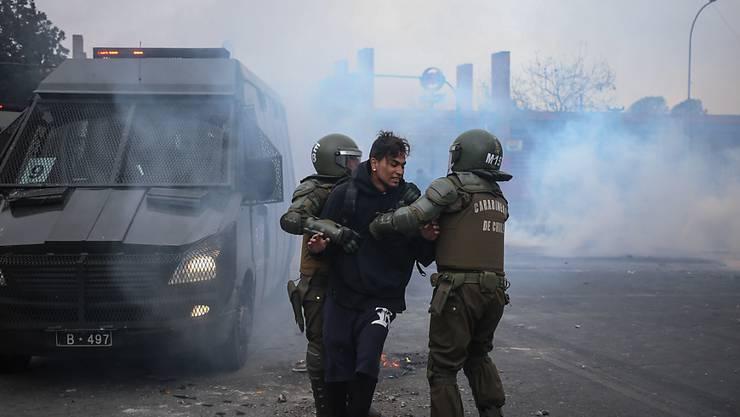 Nach schweren Ausschreitungen bei einer Demonstration zum Jahrestag des Staatsstreichs in Chile nehmen Polizisten einen Mann fest.
