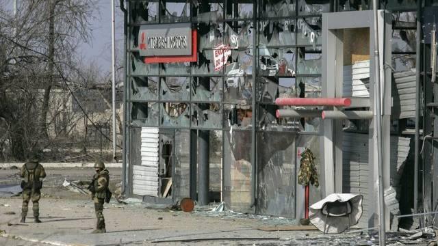 Rebellen stehen am Samstag vor einem zerbombten Gebäude in Donezk