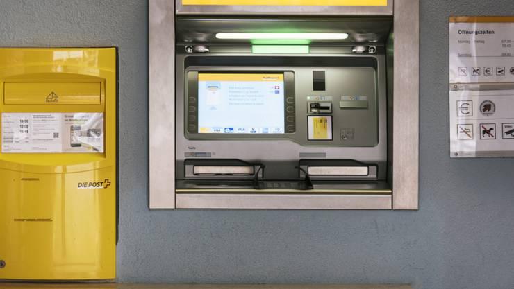 Ein Briefkasten und ein Geldautomat vor einer Filiale der Schweizerischen Post am Toblerplatz in Zürich. (Archiv)