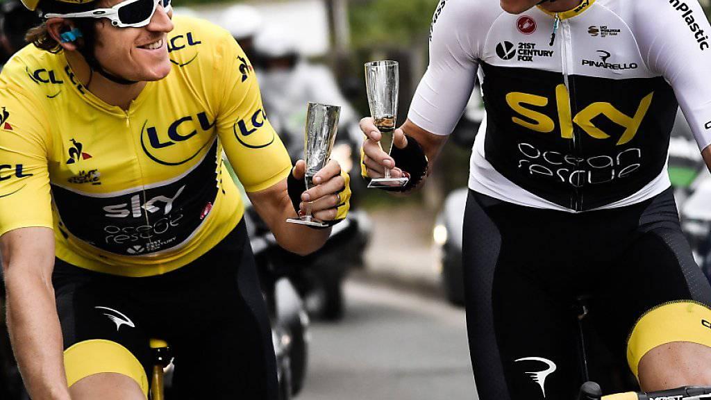 Geraint Thomas (links) und Chris Froome genehmigen sich in der letzten Etappe der Tour de France 2018 ein Glas Sekt. Auch 2019 werden die beiden Briten gemeinsam an der Frankreich-Rundfahrt starten