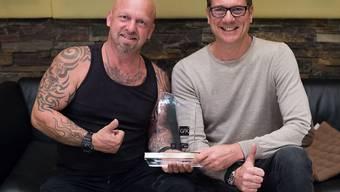 """Gölä (links) hat den """"Nummer 1 Award der Offiziellen Schweizer Hitparade"""" am Montag in Thun aus den Händen von Andy Renggli, General Manager Schweiz GfK Entertainment, entgegen genommen"""
