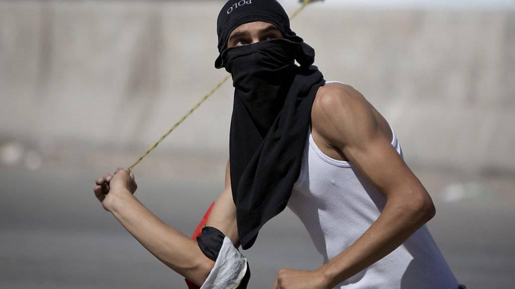 Ein Palästinenser greift israelische Sicherheitskräfte mit einer Steinschleuder an: Israel verschärft sein Vorgehen gegen Steinwerfer. (Archivbild)