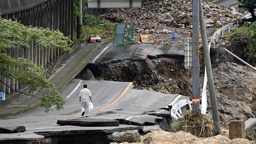 Ein Mann geht auf einer stark beschädigten Straße. Rekordstarke Regenfälle hatten am Wochenende schwere Überflutungen und Erdrutsche im Südwesten Japans ausgelöst.