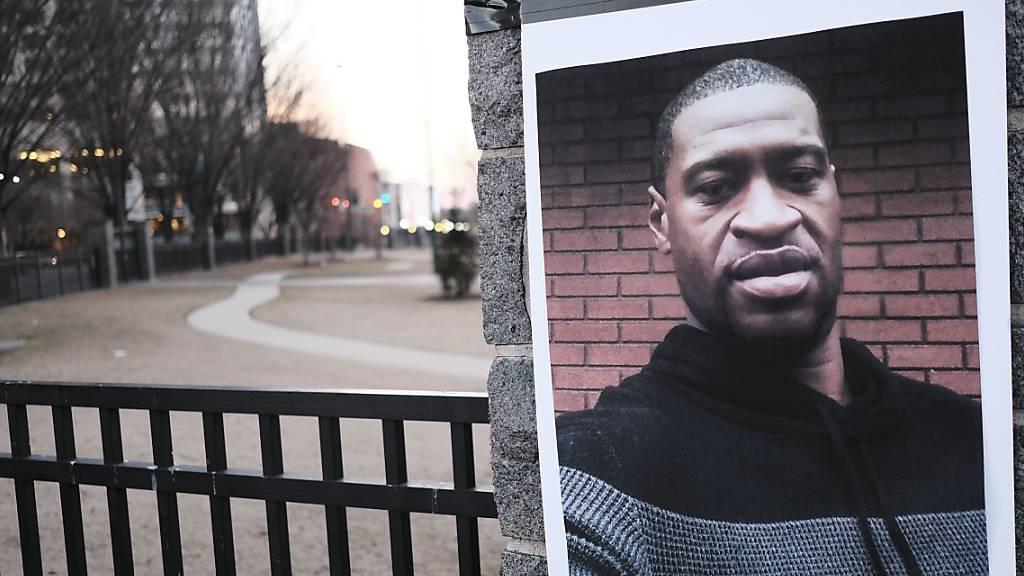 Ein Bild von George Floyd ist an einem Pfeiler angebracht. Fast ein Jahr nach der Tötung des unbewaffneten Afroamerikaners George Floyd bei einem Polizeieinsatz hat in Minneapolis, USA, der Prozess gegen den weißen Hauptangeklagten Chauvin begonnen. Foto: John Arthur Brown/ZUMA Wire/dpa
