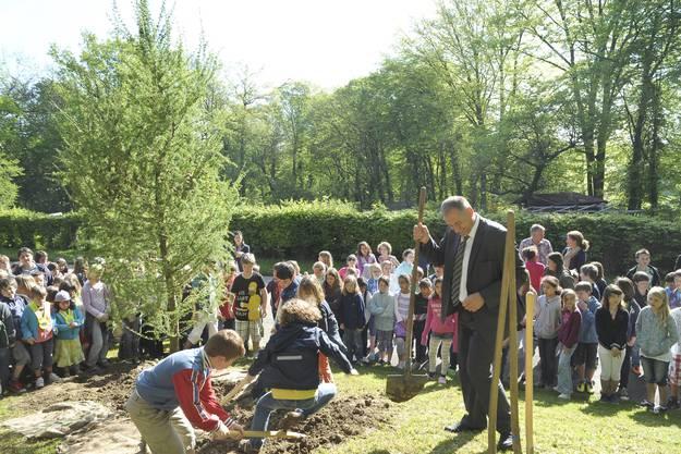 Hans-Peter Wessels pflanzt zusammen mit den Kindern den Baum ein.