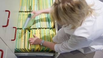 Eine medizinische Praxisassistentin sucht eine Patientenakte heraus (Symbolbild)